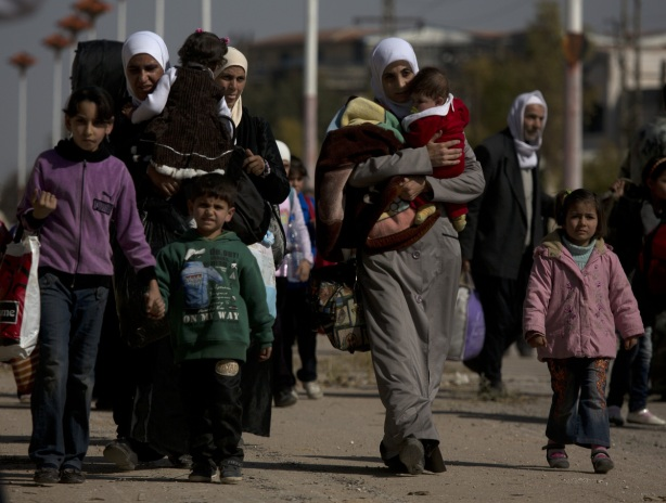 Women and children walk from the rebel held suburb of Moadamiyeh to the government held territory Tuesday Oct. 29, 2013 in Damascus, Syria. (AP Photo/Dusan Vranic)