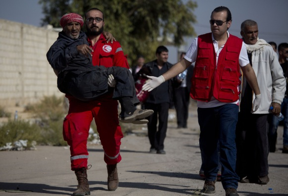 A man is helped by a Red Crescent worker on his way from the rebel held suburb of Moadamiyeh to the government held territory Tuesday Oct. 29, 2013 in Damascus, Syria. (AP Photo/Dusan Vranic)