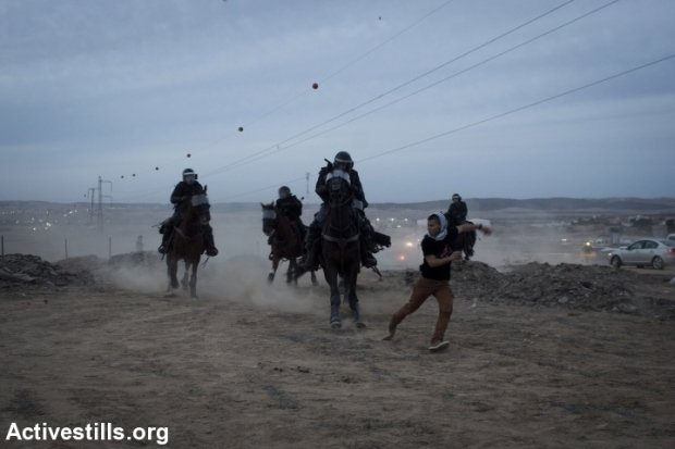 Mounted Israeli policemen chase a Bedouin youth during a protest against the Israeli government's Prawer Plan, on road 31 on November 30, 2013 near the town of Hura, Israel. (+972 Magazine)