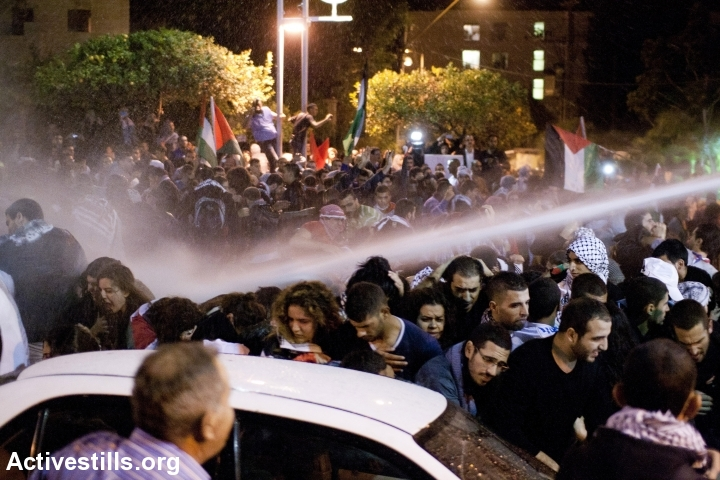 Demonstrators run away from a police water canon during a Day Of Rage protest against the Prawer-Begin Plan, Haifa, Israel, November 30, 2013. (+972 Magazine)
