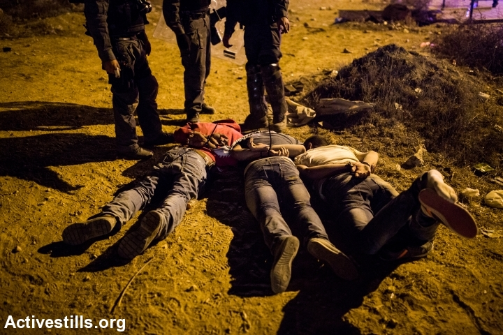 Three arrested Beduin youth laying on the ground hand cuffed during a police raid on the main road on the town of Hura, after a Day of Rage protest, November 30, 2013. (+971 Magazine)